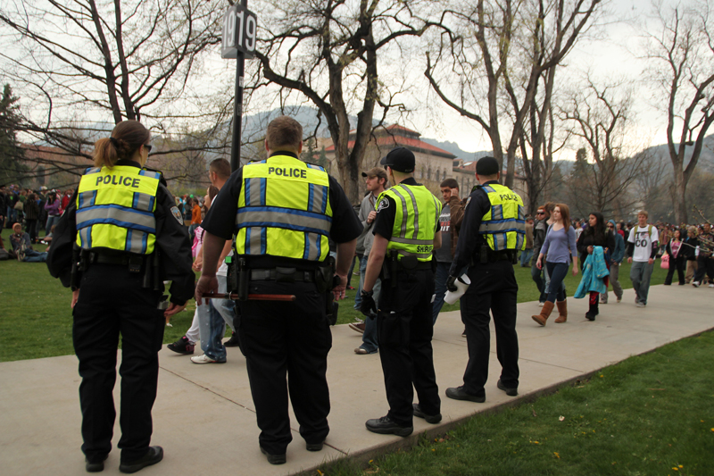 "Police officers watch as the 4/20 crowd begins to leave Norlin Quad in 2011. CU spokesperson Bronson Hilliard said, ""The goal is not to remove 4/20 by force"" in the future. (CU Independent File/Robert R. Denton)"