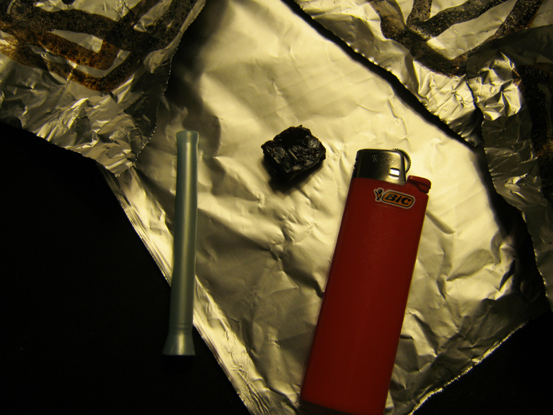 A piece of black tar heroin sits on a sheet of foil next to Suzy's lighter and pipe (CU Independent/Sebastian Murdock)
