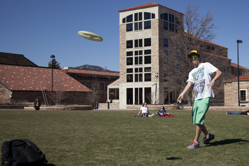 Freshman MCDB major Nathan Anderson, 18, tosses a frisbee on Farrand Field on Friday. The warm weather attracted many people to Farrand who did everything from sit and read to play soccer. (CU Independent/Robert R. Denton)