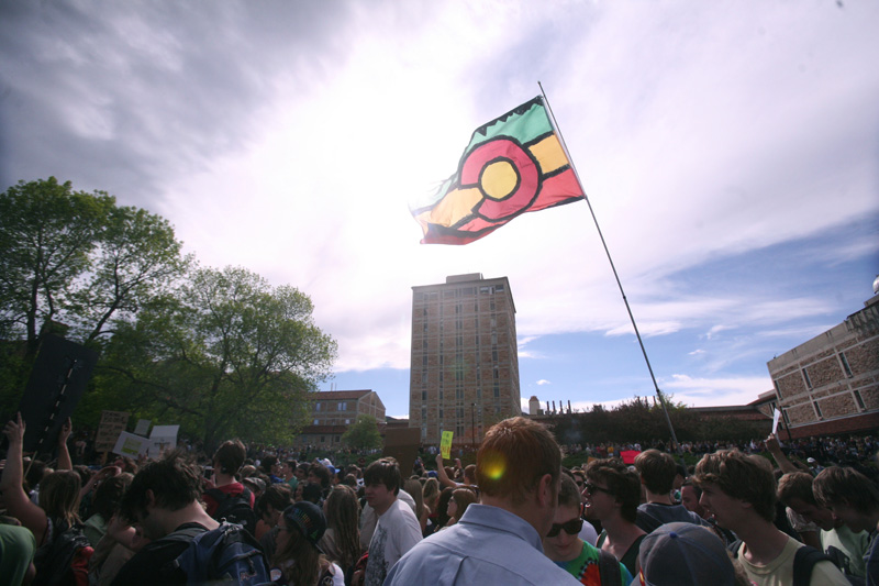 A rasta-colored Colorado state flag soars above the crowd at 4:20 p.m. on the Duane Physics lawn. (CU Independent/Nate Bruzdzinski)