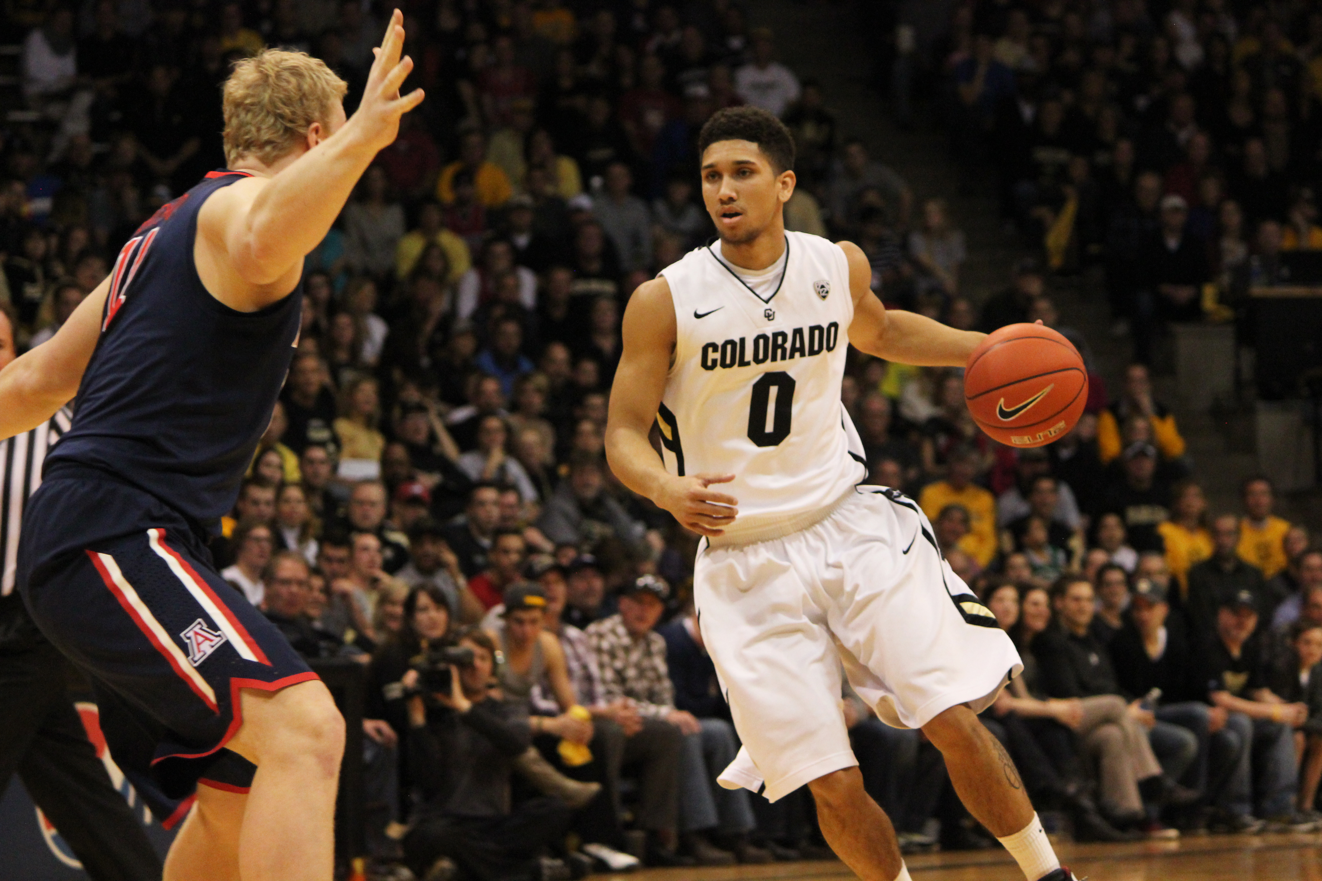 Colorado guard Askia Booker looks to drive into the lane against Arizona defender Kyryl Natyazhko on Saturday afternoon. Booker scored 9 points on the night, making 4 of 6 free throws. (Kai Casey/CU Independent)