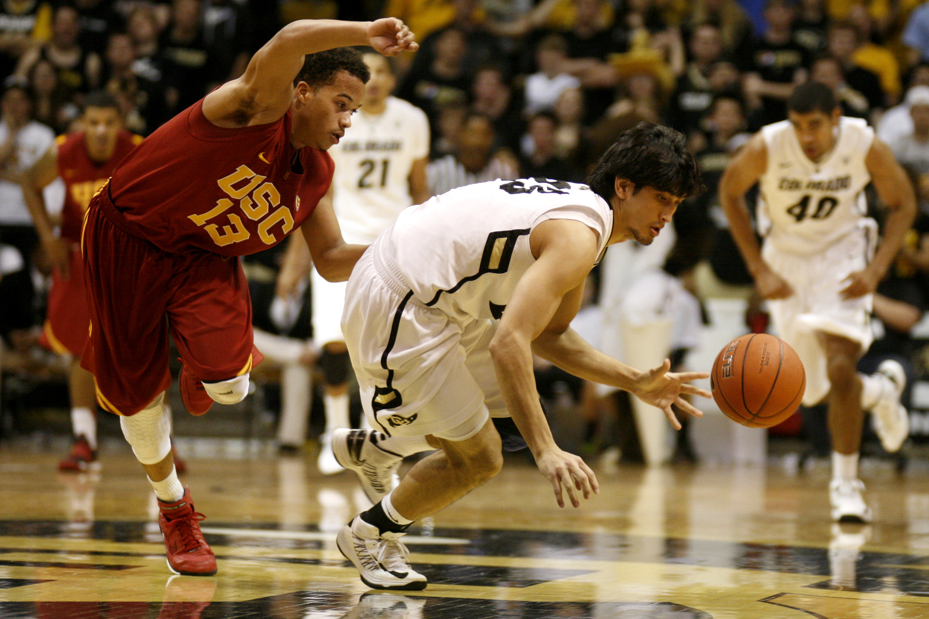 Senior guard Sabatino Chen beats USC's Chass Bryan to a loose ball during a game against USC at the Coors Events Center on Thursday, Jan. 10, 2013. (Kai Casey/CU Independent)