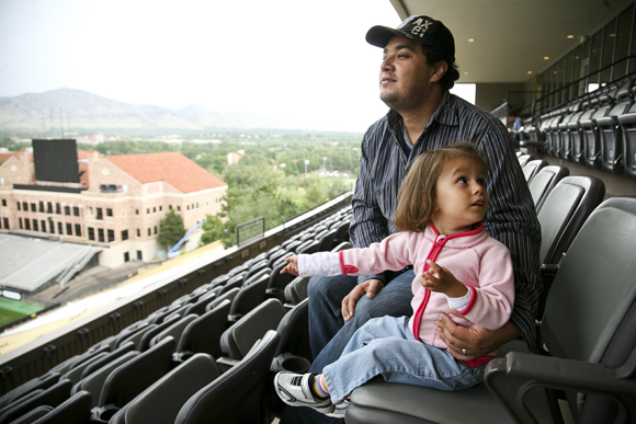 Francisco Sanchez sits with his daughter Aylin, 3, at the club level of Folsom Field, Saturday, Sept. 14, 2013. Several CU athletes, including football players, served lunch to flood victims to provide relief. Heavy rains and flooding caused the football game between the University of Colo. and Fresno State to be postponed. This was only the third time in CU history that a football game has been postponed. The first two were after President John F. Kennedy was assassinated in 1963 and the game after the Sept. 11 attacks. (Kai Casey/CU Independent)