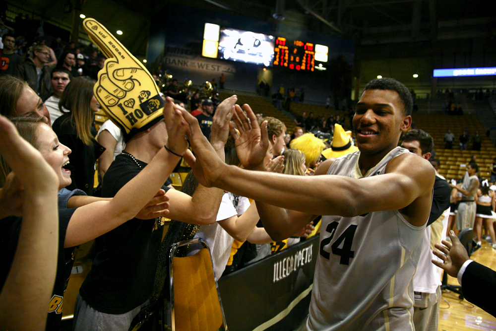 Freshman George King (24) smiles as he high-fives fans after the win against Wyoming on Nov. 14 2013. King redshirted for the 2014-2015 season. (Kai Casey/CU Independent File)