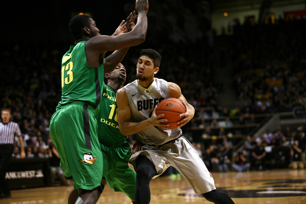 Colorado junior guard Askia Booker grimaces while trying to push through Oregon defenders Johnathan Loyd (10) and Richard Amardi (13). (Kai Casey/CU Independent)