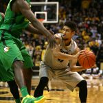 Colorado junior guard Askia Booker (0) looks to pass around an Oregon defender. (Kai Casey/CU Independent)
