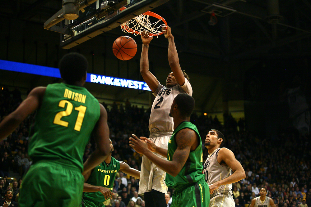 Colorado sophomore forward Xavier Johnson (2) dunks the ball above a host of players. (Kai Casey/CU Independent)