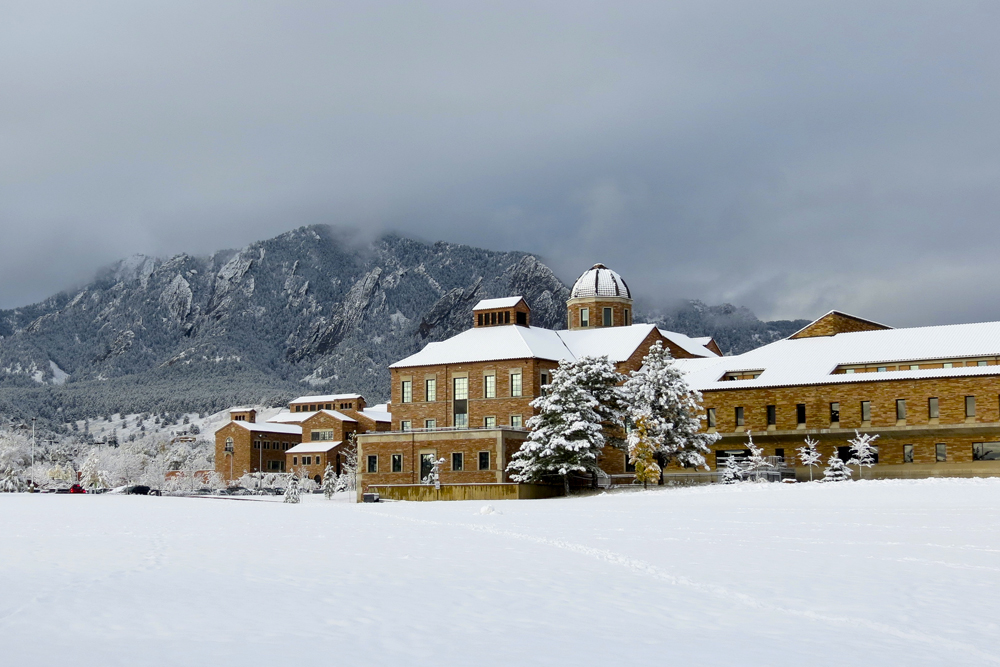 The Koelbel Building sits under a blanket of snow in front of the Flatirons. (Matt Sisneros/CU Independent)