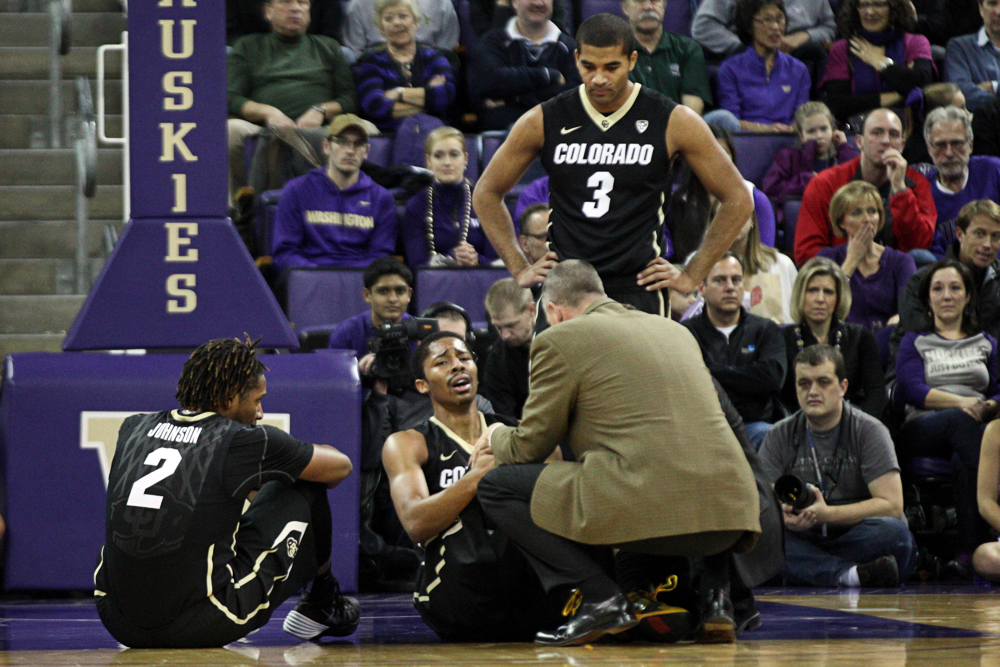 Junior guard Spencer Dinwiddie (25) grimaces after injuring his knee while head coach Tad Boyle, sophomore guard Xavier Talton (3) and Xavier Johnson (2) look on in the first half against Washington, Sunday in Seattle, Wash. Dinwiddie fell to the ground with an apparent knee injury after making a cut while driving to the hoop. (Photo Courtesy of Kyu Han/The Daily)