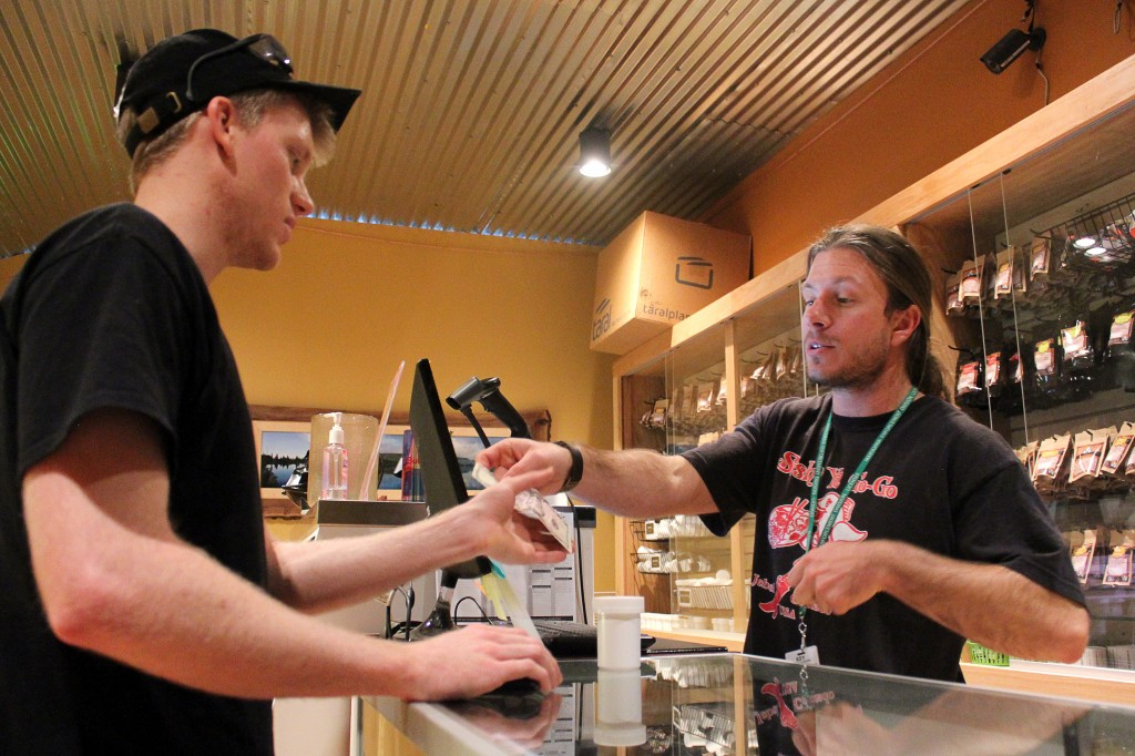 Justin Lapenter, right, a bud tender, gives Chris Horner, a Colorado State graduate who now lives in Niwot, change back after Lapenter bought his first legal weed at the Terrapin Care Station, Tuesday, Feb. 18, 2014, in Boulder, Colo. Recreational weed must be purchased with cash. The Terrapin Care Station, located at the corner of Folsom Street and Canyon Boulevard, was the first recreational pot shop to open in the city of Boulder. Karing Kind, a recreational pot shop north of Boulder, was the first to open in Boulder County. (Kai Casey/CU Independent)