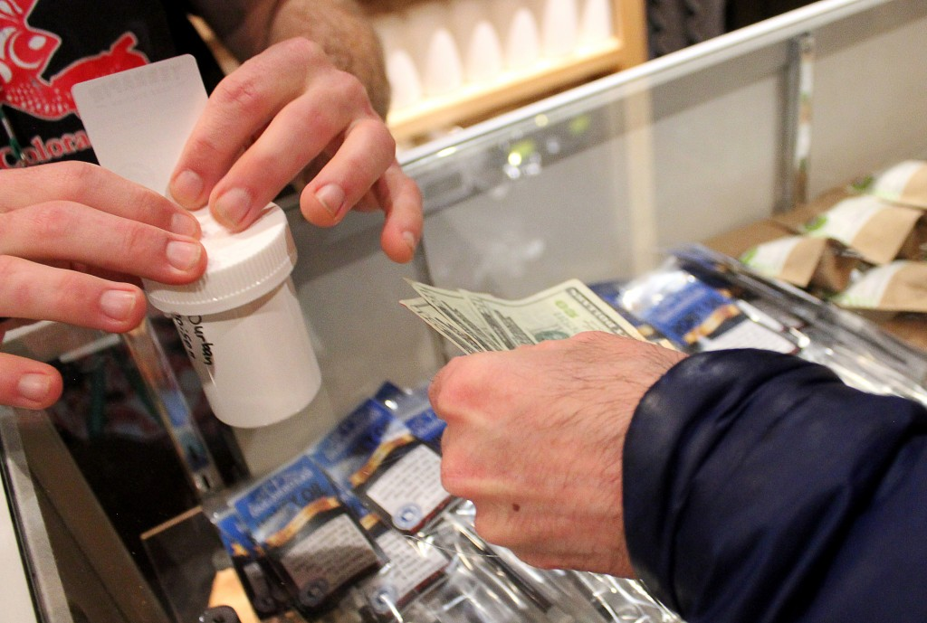 A customer purchases a container of weed with cash at the Terrapin Care Station, Tuesday, Feb. 18, 2014, in Boulder, Colo. Recreational pot has to be purchased with cash. The Terrapin Care Station, located at the corner of Folsom Street and Canyon Boulevard, was the first recreational pot shop to open in the city of Boulder. Karing Kind, a recreational pot shop north of Boulder, was the first to open in Boulder County. (Kai Casey/CU Independent)