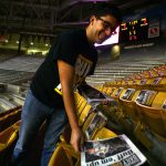 Ian Solow-Niederman, executive director of the C-Unit, lays newspaper on every seat in the first 15 rows of the east side of the Coors Events Center for students to use during the College GameDay broadcast. (Kai Casey/CU Independent)