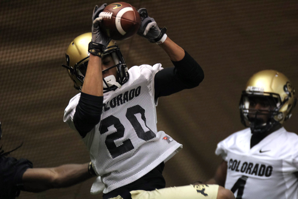 Junior defensive back Greg Henderson intercepts a pass thrown by freshman quarterback Sefo Liufau at practice on March 7, 2014. Henderson will start at cornerback again for his upcoming senior season. (Matt Sisneros/CU Independent)