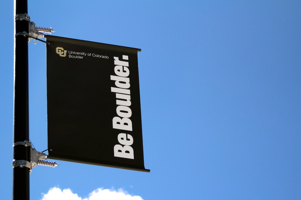 "A ""Be Boulder"" sign hangs on a pole near the Center for Community building on campus.  (Calyx Ward/CU Independent)"