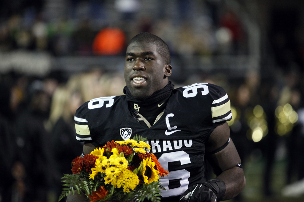 Senior defensive lineman Chidera Uzo-Diribe (96) smiles as he runs onto the field during a senior ceremony, Nov. 24, 2013, in Boulder, Colo. (Robert R. Denton/CU Independent)