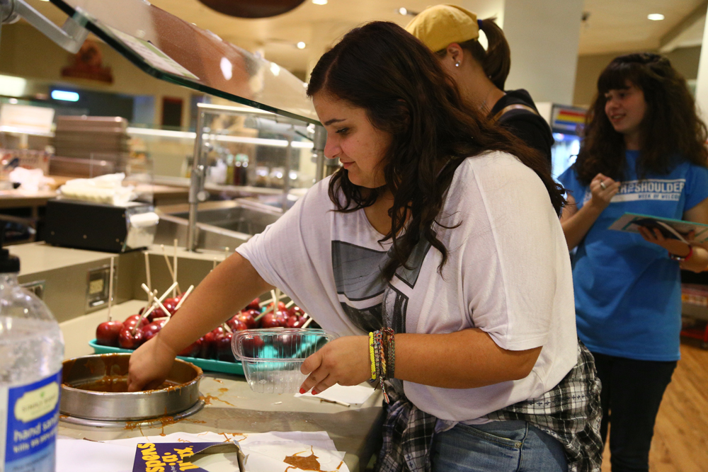 A student dips a caramel apple in the Alfred Packer Grill during WelcomeFest. (Nigel Amstock/CU Independent/File)