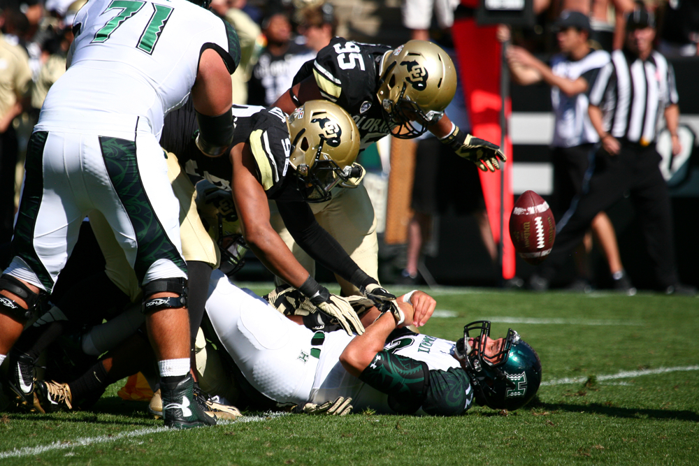 Hawaii senior quarterback Jeremy Higgins (12) loses the ball after being hit by Colorado's Jimmie Gilbert (98) and Derek McCartney (95) during an NCAA football game between the Colorado Buffaloes and the Hawaii Rainbow Warriors on Saturday at Folsom Field in Boulder, Colo. The Buffs won 21-12, getting their first home win of the season. The Buffs didn't give up a touchdown on Saturday, but they might have to play even better this week with Cal averaging 44 points per game. (Kai Casey/CU Independent)