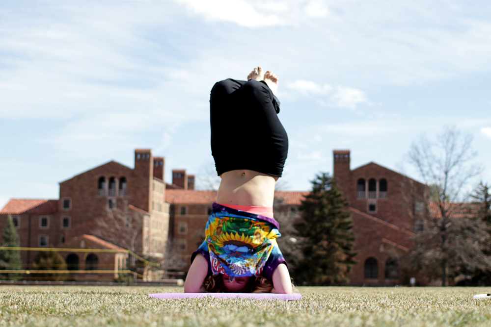 """Emily Kathrine, a sophomore at CU, practices yoga on Farrand Field in 2014. """"Yoga is a good way to get every muscle in your body working, and to find balance within yourself,"""" Kathrine said. (Calyx Ward/CU Independent)"""