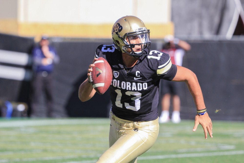 Quarterback Sefo Liufau scrambles while looking for an open receiver at Folsom Field on Oct. 25, 2014. (Nigel Amstock/CU Independent File)
