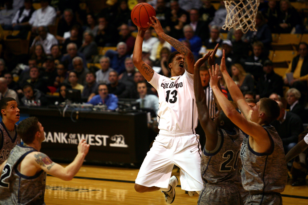 Colorado sophomore forward Dustin Thomas (13) skies over two Air Force defenders for a layup during an NCAA men's basketball game between Colorado and Air Force, Tuesday, Nov. 25, 2014, at the Coors Events Center in Boulder, Colo. (Kai Casey/CU Independent)