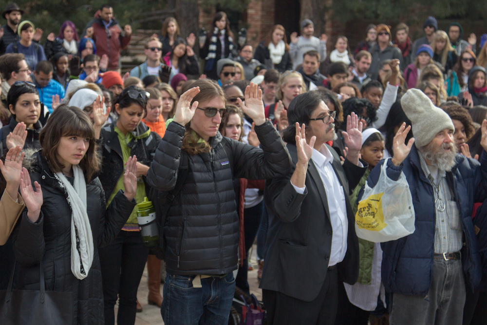 "CU students and Boulder residents participate in a Ferguson protest with the ""hands up, don't shoot"" pose at the UMC fountain at 11 a.m. on Dec. 1, 2014. (Matt Sisneros/CU Independent File)"