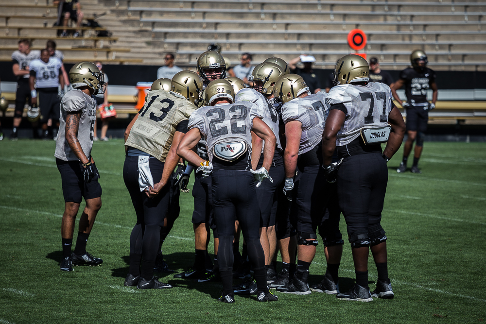 CU's first team offense huddles up during an intrasquad scrimmage on Folsom Field during Fall Camp 2015. (Matt Sisneros/CU Independent)