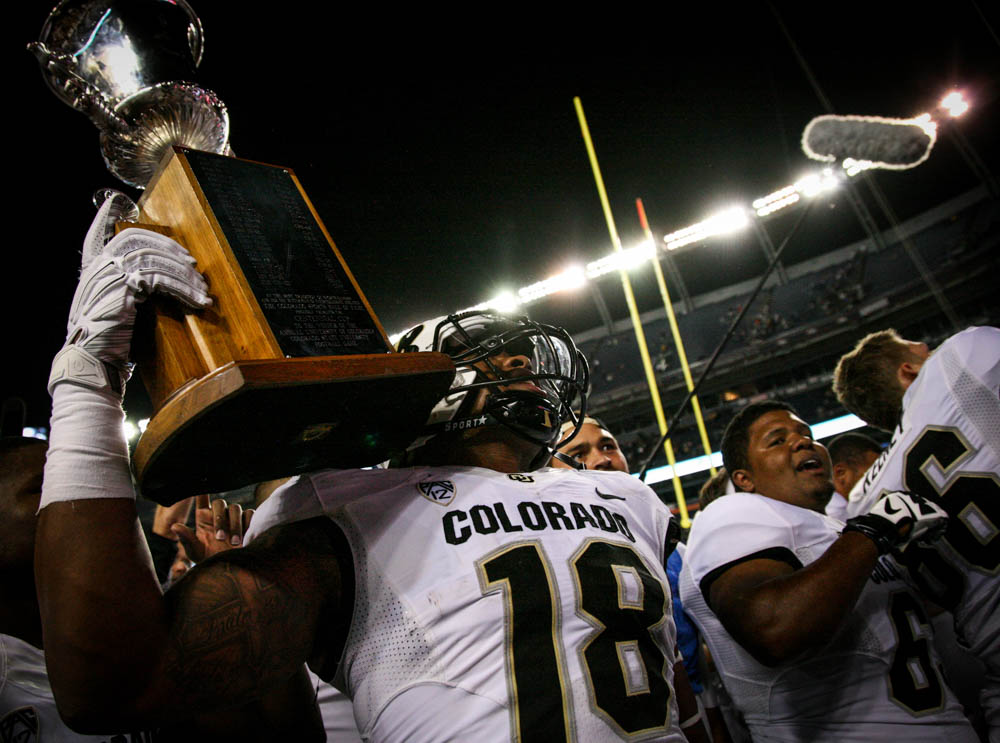George Frazier (18) holds the trophy high after defeating the Rams Saturday night 27-24 during the Rocky Mountain Showdown that went into nail-biting over-time. (Danny Anderson / CU Independent File)