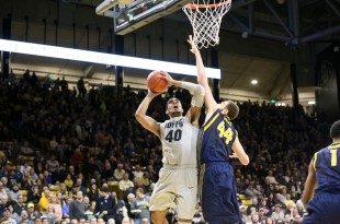 Senior forward Josh Scott looks to shoot the ball over a Cal defender early in the second half of play at the Coors Events Center on Jan. 31, 2016. (Nigel Amstock/CU Independent File)