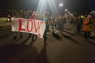"""Students led by a banner reading """"Love"""" march down 28th Street toward Colorado Avenue as they protest the election of Donald Trump. Nov. 11, 2016. (Ellis Arnold/CU Independent)"""