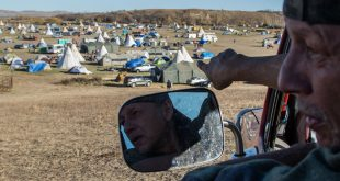 """Sam """"Hughie"""" Nelson points to the Oceti Sakowin Camp from a hill dubbed """"Facebook hill"""" in late October 2016. (Jackson Barnett/CU Independent)"""