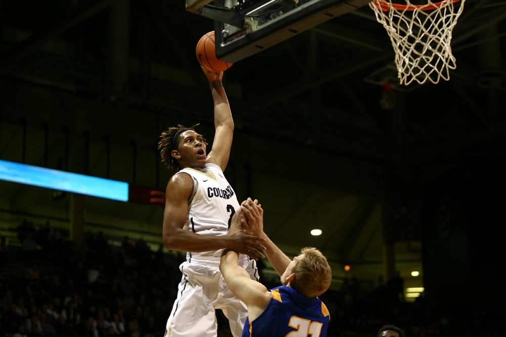 Sophomore forward Xavier Johnson (2) skies for a dunk over UCSB's Mitch Brewe (21). (Kai Casey/CU Independent)