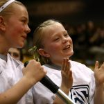 Pac-12 court shiner crew members smile as they cheer on Colorado. (Kai Casey/CU Independent)