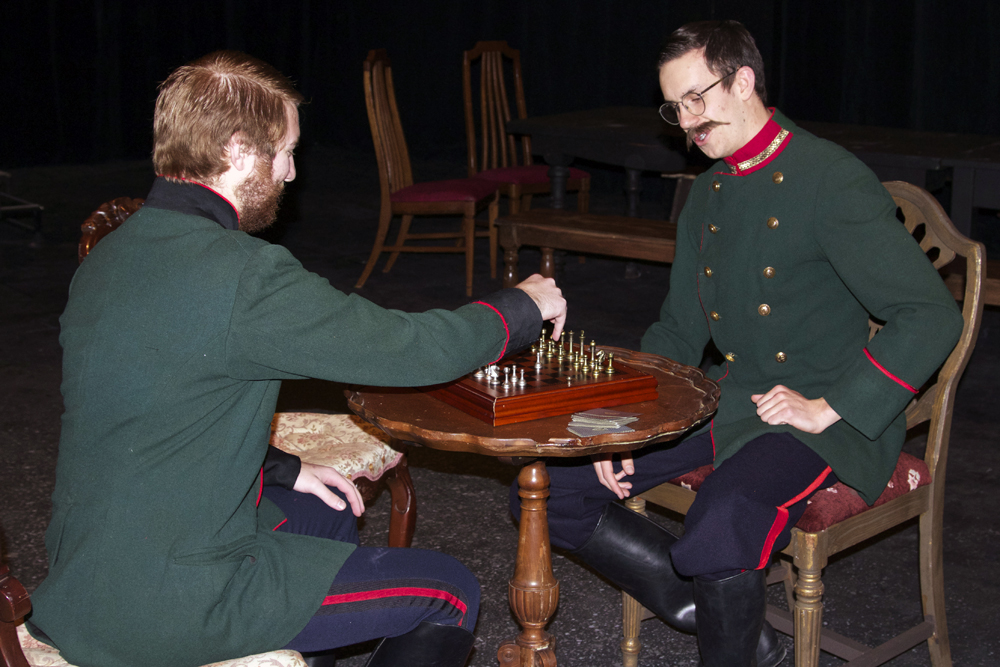 Junior Eddy Jordan, right, and freshman Greg Baker, left, play chess during a practice of Act 1 of the Three Sisters Production before a dress rehearsal on Wednesday night. Jordan and Baker play a soldiers in this upcoming weeks play. (Calyx Ward/CU Independent)