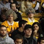 """Two Colorado fans sit in the stands dressed as """"The Twins,"""" the two eighty-eight year old ladies who attend every CU sporting event, during the ESPN College GameDay broadcast at the Coors Events Center, Saturday, Feb. 22, 2014, in Boulder, Colo. (Kai Casey/CU Independent)"""