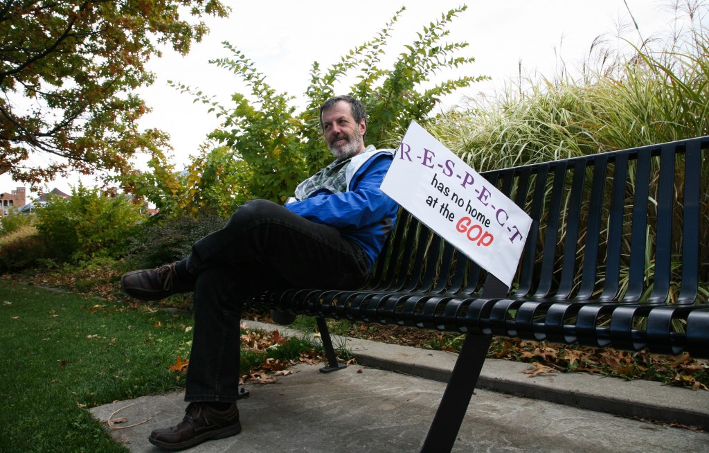 A man sits on a bench with his sign near Farrand Field before the GOP debate in Boulder, CO Wednesday night. (Danny Anderson/CU Independent)