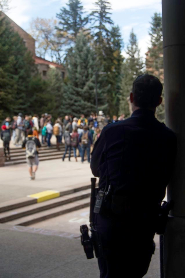 An officer of the law looking on at the crowd of students being preached at by extremist Christians. (Vincent Guielo/CU Independent)