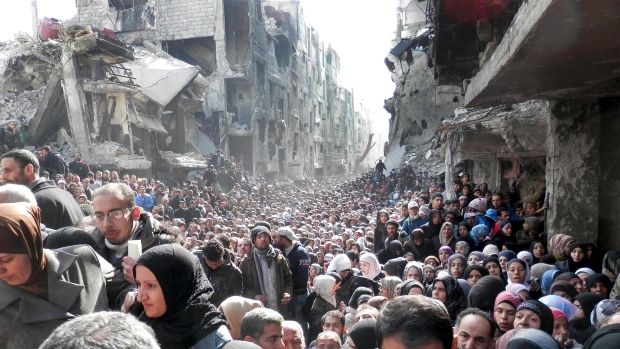 This picture taken on Jan. 31, 2014, and released by the United Nations Relief and Works Agency for Palestine Refugees (UNRWA), shows residents of the besieged Palestinian camp of Yarmouk, queuing to receive food supplies, in Damascus, Syria (UNRWA via AP, File)