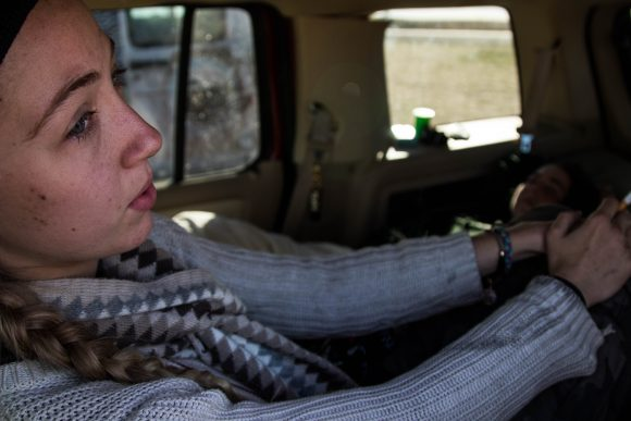 Emily smokes a cigarette in the back of her car at the Dakota Access Pipeline protests in late October. (Jackson Barnett/CU Independent)
