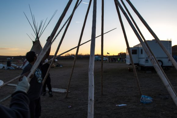 After a few hours of struggling, David Sage, and Jesse finish the frame of David's teepee at the Dakota Access Pipeline protest camp. (Jackson Barnett/CU Independent)