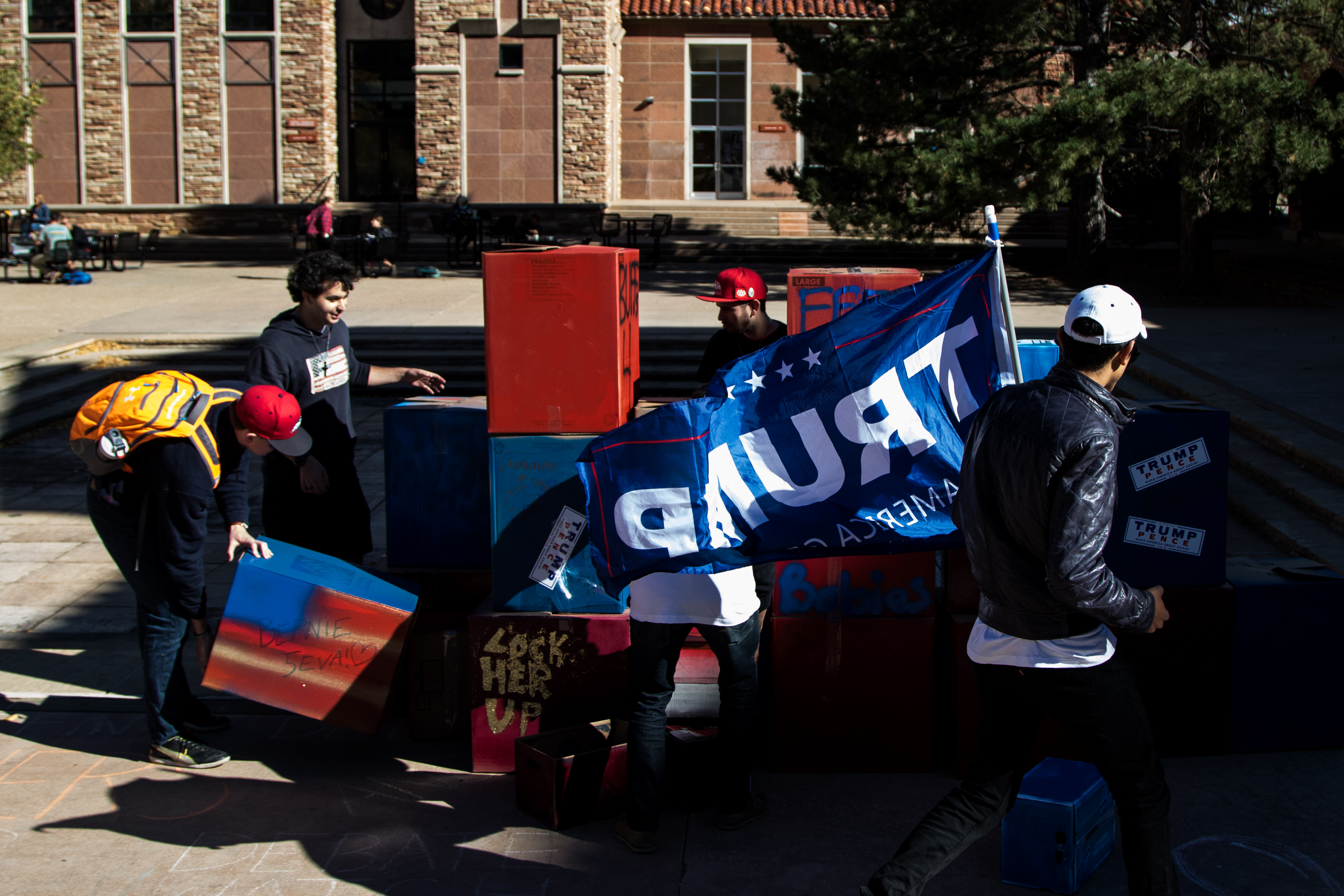 "Trump supporters on campus erect a ""free speech wall"" modeled after Trump's proposed border wall. Many students booed at their showing of support for Trump, one student even took to kicking over the cardboard boxes that they made their wall out of. (Jackson Barnett/CU Independent)"