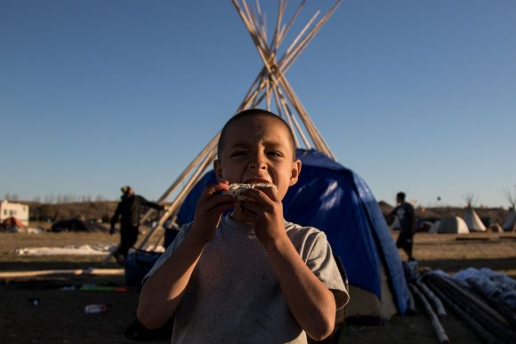 Kaslin's friend bites into a raw ramen packet as David and Sage build a teepee in the background. (Jackson Barnett/CU Independent)