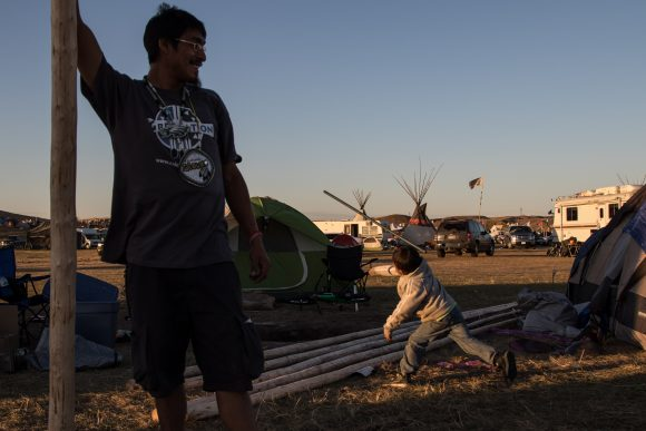 Kaslin throughs a metal dowel as a spear while roughhousing with a friend at the Dakota Access Pipeline protest camp. (Jackson Barnett/CU Independent)