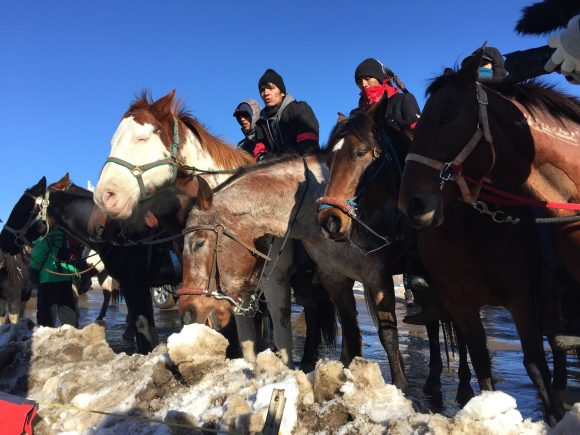 Riders arrive at the central sacred fire to celebrate the denied Dakota Access Pipeline easement on Sunday, Dec. 4th. (Photo courtesy of Charles McGuire Wien)