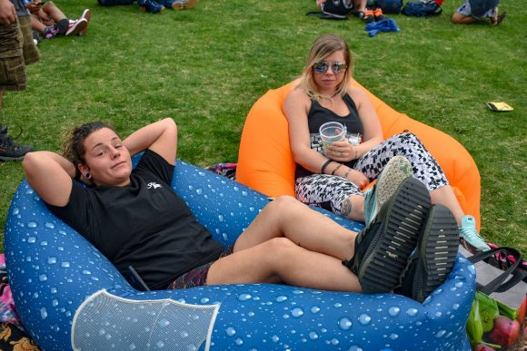 Two Mile High Festival 2019 attendees lounging in inflatable lounge chairs.