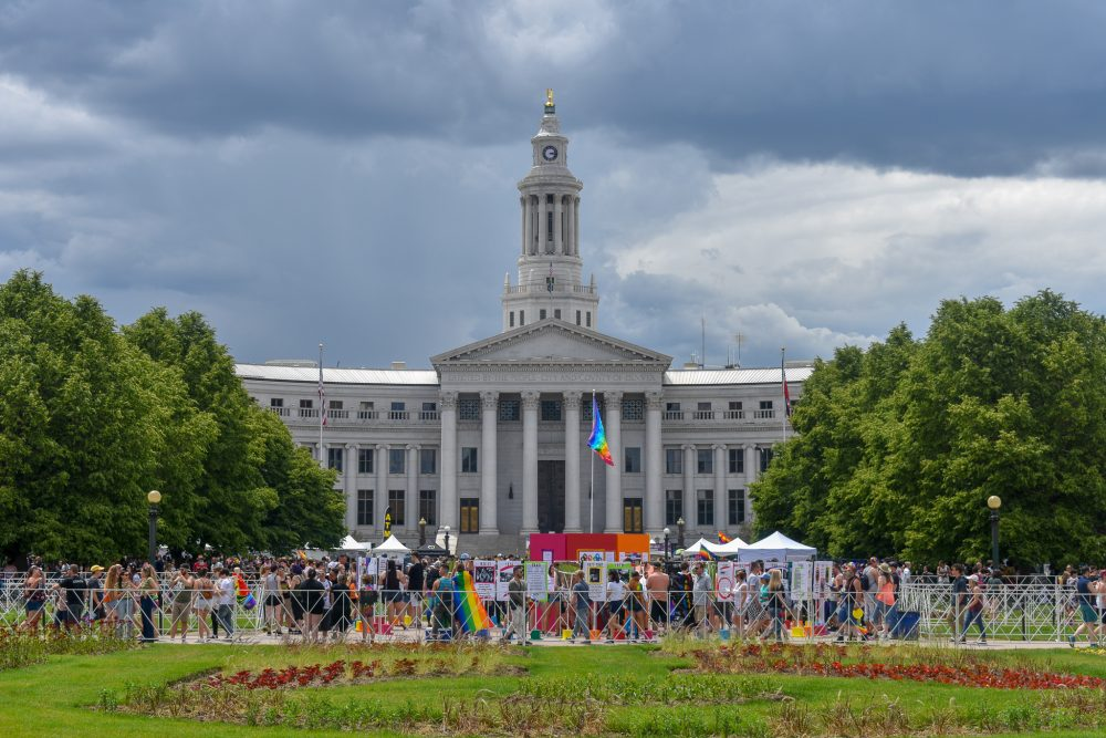 Attendees gather in front of the Denver City Hall and County Building to celebrate Denver PrideFest.